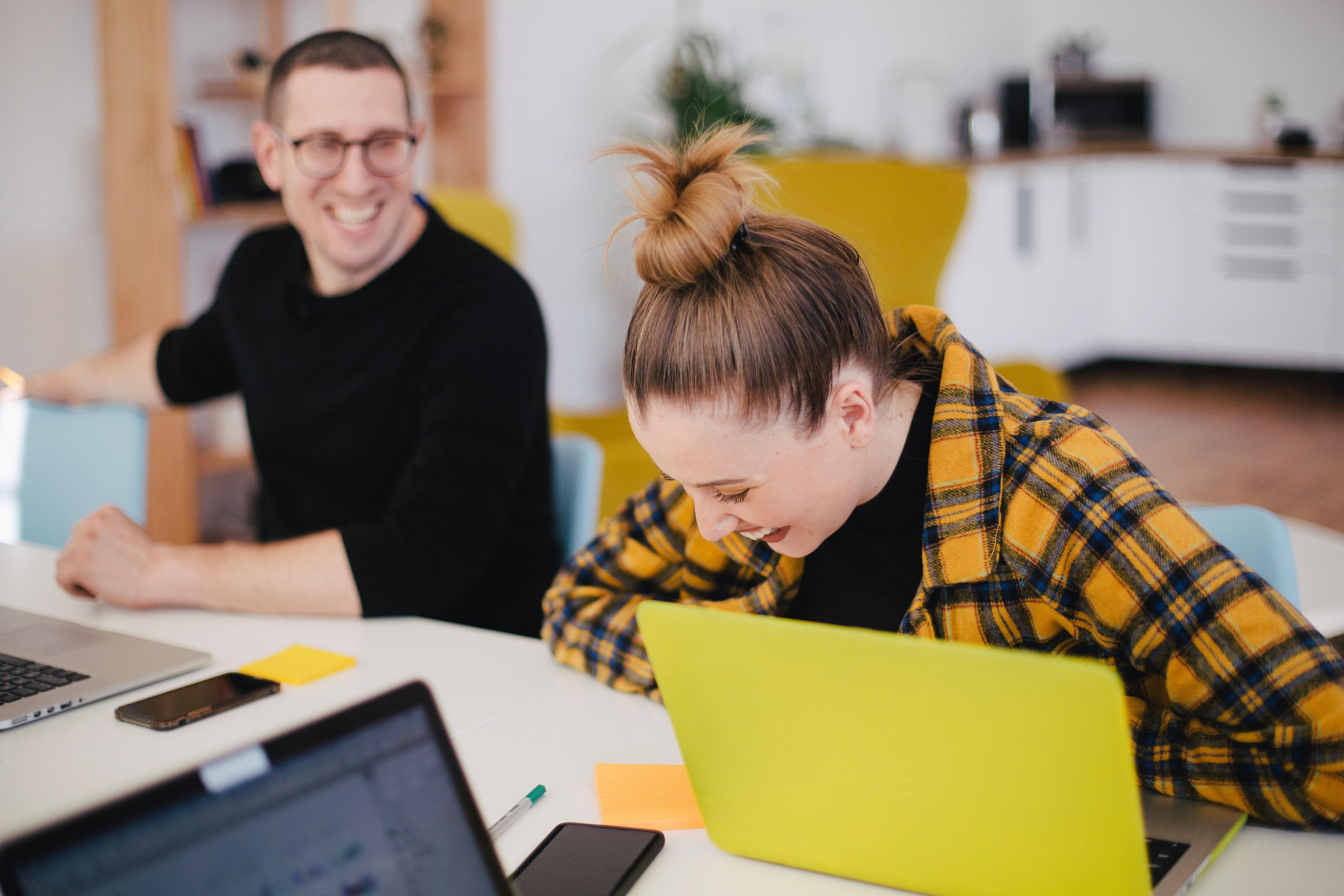 Tietokoneiden äärellä iloisesti työskentelevä nainen ja mies