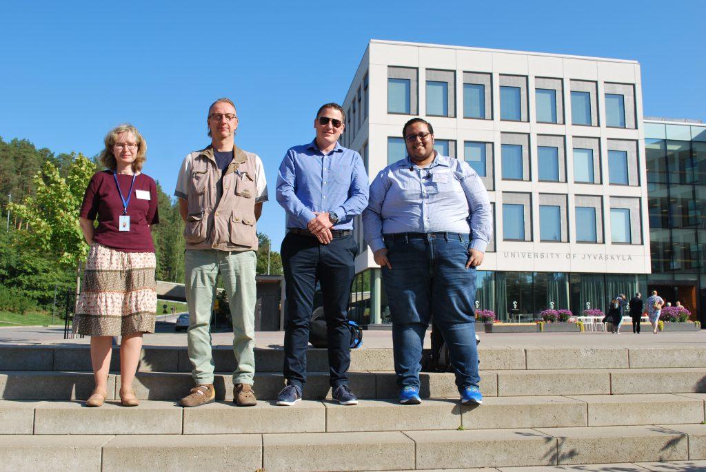 Photo of four rewarded proposers taken in front of University of Jyväskylä: Judit Hahn, Mikko Romppainen, Rune Andersen and Adithya Varadarajan.