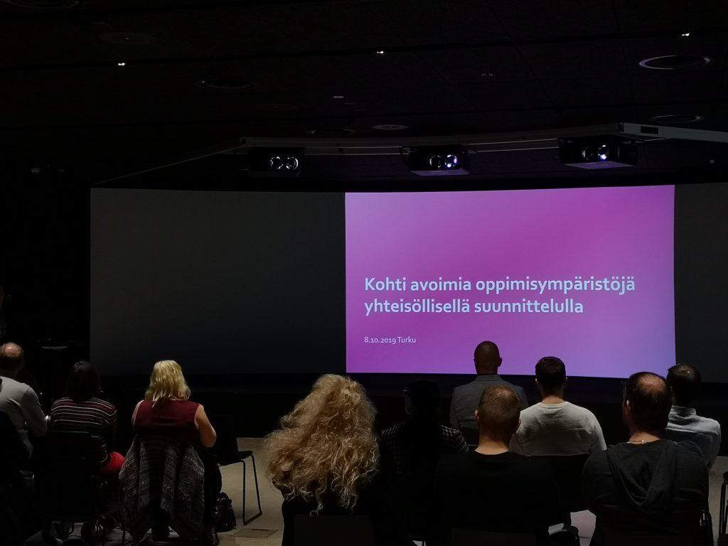 Valokuva DigiKilta-seminaarista. Esitysdioissa teksti Kohti avoimia oppimisympäristöjä yhteisöllisellä suunnittelulla.