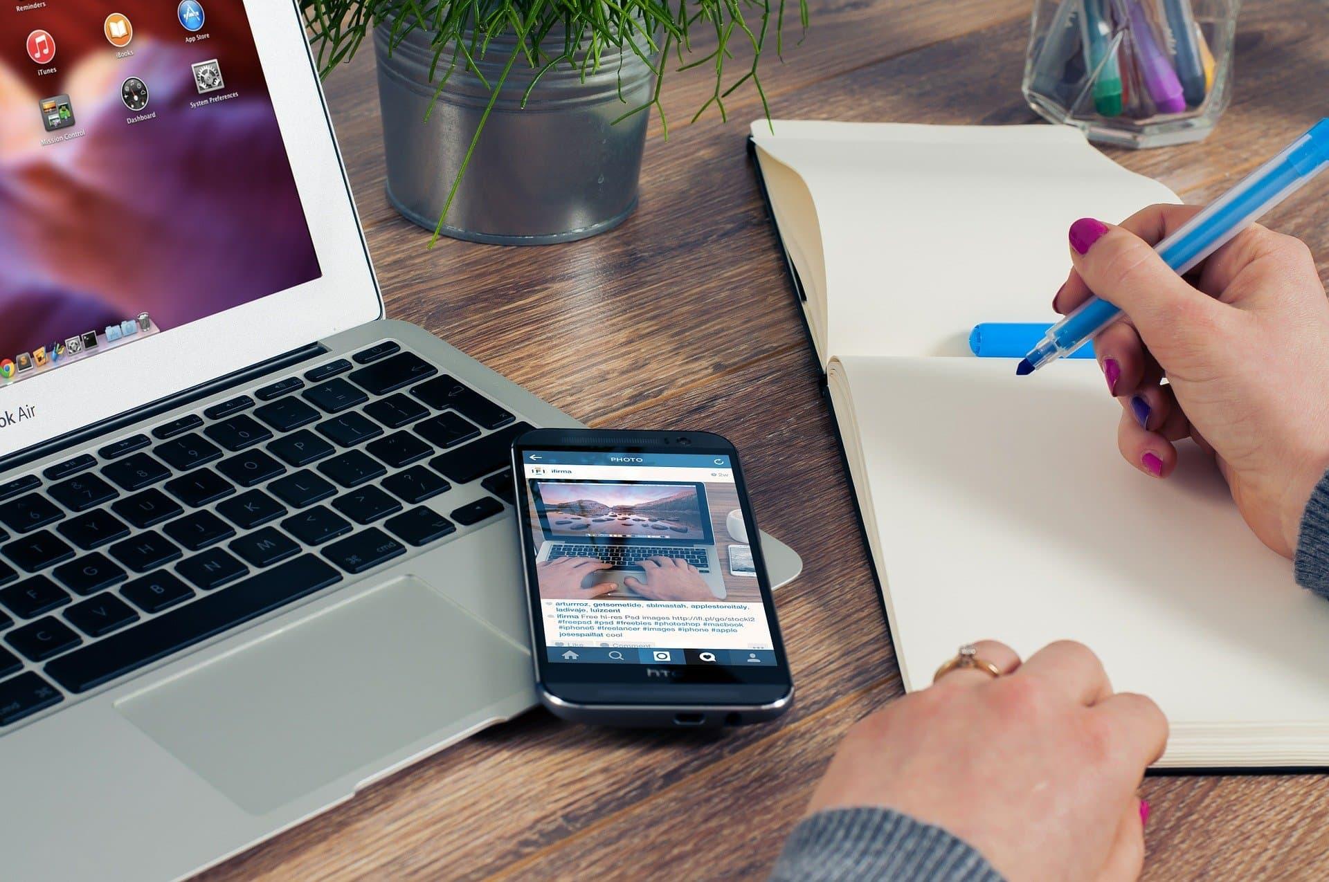 Kynä kädessä muistikirjan äärellä, vieressä kannettava tietokone ja mobiililaite