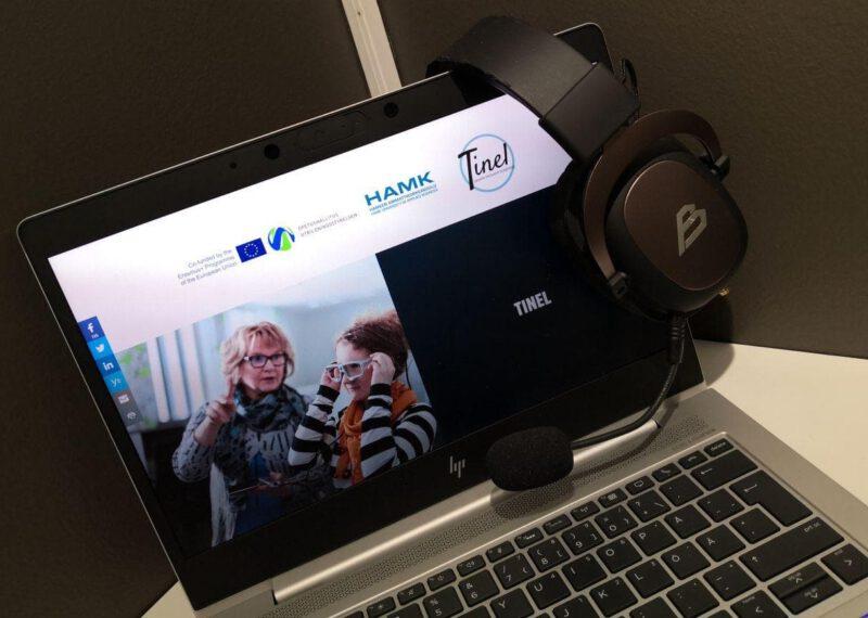 Tinel-hankkeen verkkosivut auki kannettavan tietokoneen näytöllä, jonka päälle ripustettu sankaluurit
