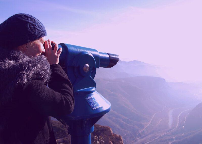 Nainen katsoo ison kaukoputken läpi vuoristosta laaksomaisemaa