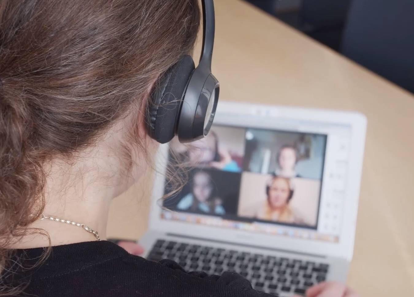 Olan yli napattu valokuva nettioppitunnille osallistuvasta henkilöstä. Kannettavan näytöllä 4 osallistujaa.