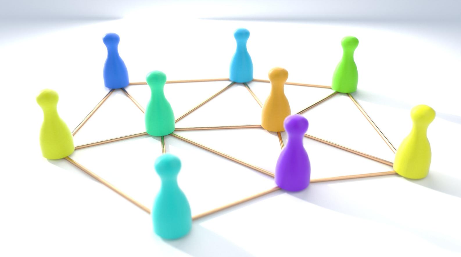 Värikkäitä pelinappuloita verkostokuvan päällä.